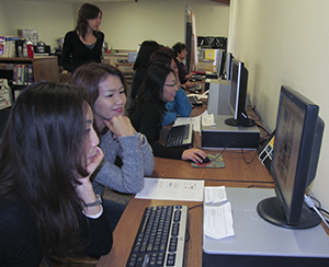 LLC Patrons Seated at Public Computers; Public Training Specialist Overseeing the Class
