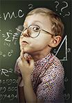 Young Boy in Front of a Chalkboard with Scientific Formulas