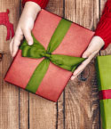 Hands Holding Gift Wrapped in Red with Green Ribbon