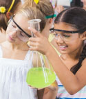 Two Girls with Safety Glasses Looking at Beakers
