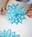 Child's Hands Holding Blue Paper Snowflake