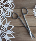 Paper Snowflakes and Scissors on a Wooden Surface