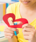 Girl Cutting Heart Out Of Red Paper