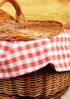 Picnic Basket with Red Gingham Blanket Sticking Out of It