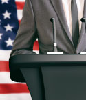 Man in Grey Suit in Front of US Flag and Behind Podium
