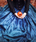 Woman in Blue Dress with Red Apple