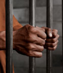 A Man's Hands Clasping Prison Bars