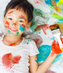 Girl Covered in Paint with Paint Brush