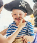 Little Boy Being Dressed Up as a Pirate