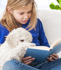 Girl Reading to Small Dog