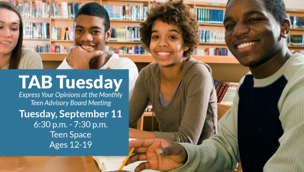 Teens Sitting at Table in Library with TAB Tuesday Information