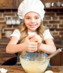 Young Girl in Chef's Hat Cracking an Egg Above a Bowl