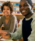 Teens Sitting at Table in Library