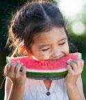 Little Girl Eating Watermelon Outside