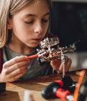 Young Girl Looking at a Mechanical Device